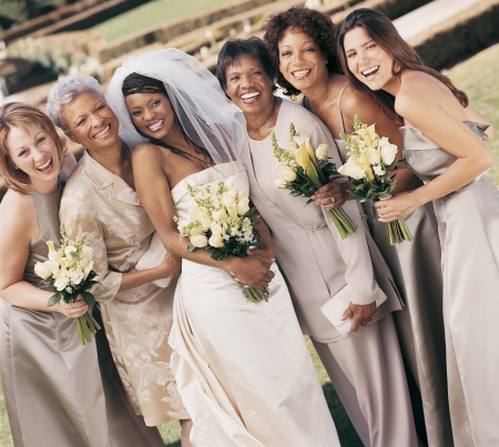 Bride, Bridesmaids and Mothers Stand Side-by-Side in the Grounds of a Wedding Reception