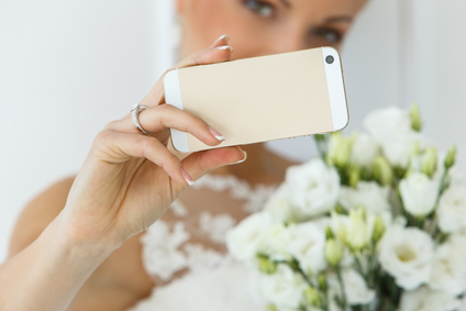 Wedding. Attractive bride with beautiful bouquet and mobile phone